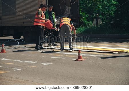 Arsenyev, Russian Federation - May 25, 2020: Workers Painting And Marking A Pedestrian Crosswalk Wit