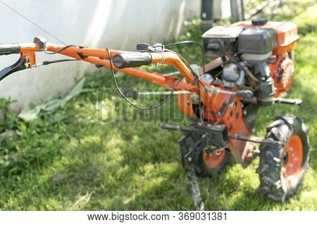 Man Farmer Plows The Land With A Cultivator. Agricultural Machinery: Cultivator For Tillage In The G