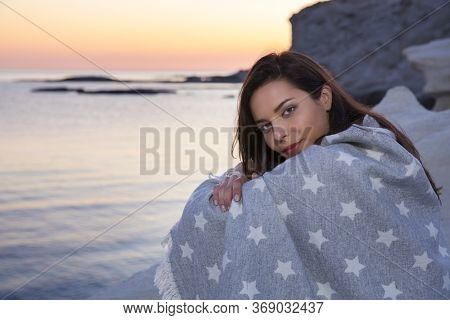 Beautiful Brunette Woman Sitting On The Beach With A Serene Sunset, Covered With Blanket.