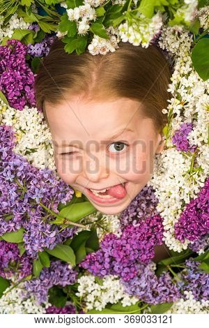 Funny Facial Portrait Of Beautiful Little Girl Winking. Teenager Wink. Teenager Girl With Bouquet Of