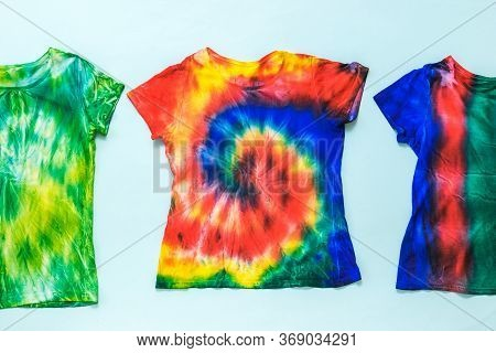 Three Tie Dye T-shirts On A Light Background. White Clothes Painted By Hand. Flat Lay. Place For Tex