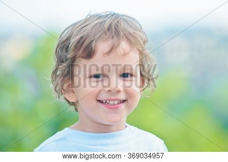 Happy Little Child Smiling. Emotions On The Face. Child Care. Portrait Little Boy Outdoor. Charming
