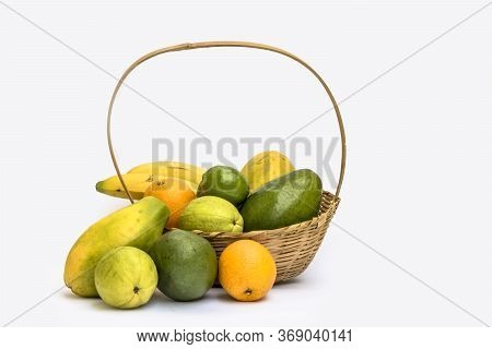 Avocado, Papaya, Orange, Banana, Guava And Lemon In A Basket Made Of Bamboo, On A White Background.