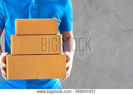 Delivery Service Courier Man Employee In Blue T-shirt Uniform Holding Empty Cardboard Boxes Or Parce