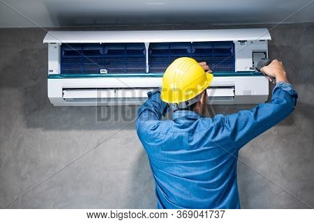 Technician Man Repairing ,cleaning And Maintenance Air Conditioner On The Wall With Screw Driver In