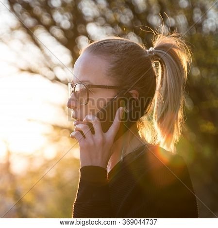 Backlit Rear View Of Young Woman Talking On Cell Phone Outdoors In Park At Sunset. Girl Holding Mobi