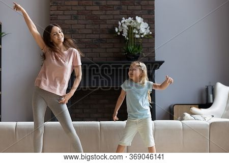 Overjoyed Young Mom Have Fun Dancing With Daughter