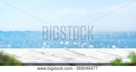 Empty White Marble Table With Blur Blue Sky And Sea Bokeh Background With Green Leaf Foreground,mock