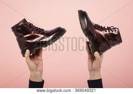 Hands Hold Boots On A Pink Background. The Concept Of Choosing Shoes, Shopping, Shoe Repair. Concept