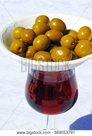 Glass Of Red Wine With Dish Of Green Olives On Top To Keep Flies Off (modern Tapas Originates From T