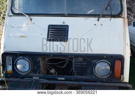 Abandoned Old White Minivan In A Junkyard