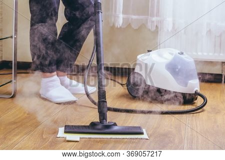 The Woman Washes The Floor In The Room With A White Steam Cleaner, A Wet High-pressure Steam. Cleani