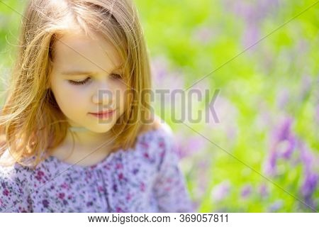 Small, Beautiful, Sad Girl Alone In A Field Of Purple Flowers. Child Is Unwell Because Of The Heat.