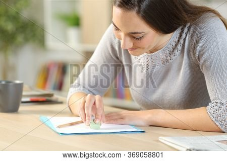 Happy Woman Erasing Pencil Marks On Paper With Rubber Sitting On A Desk At Home