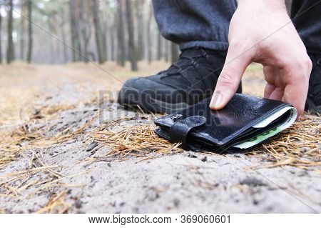 Finding A Wallet On A Forest Path When A Man Walked Through The Forest. Finding Money. Luck. Happy.