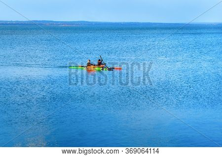 A Company Of Young People On Kayaks Is Training At Sea. A Pair Of Multi-colored Canoes Sail In The B