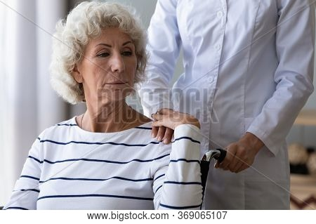 Sad Handicapped Woman Sitting In Wheelchair Holding Hand Of Caregiver