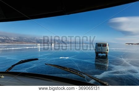 Khuzhir, Baikal, Russia - February 23 2019: View On Frozen Ice Of Baikal Lake With Local Cars Moving