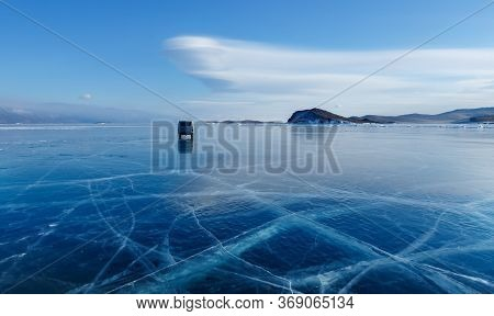 Khuzhir, Baikal, Russia - February 23 2019: Local Car Moving On Crystal Clear Ice Of Baikal Lake Wit