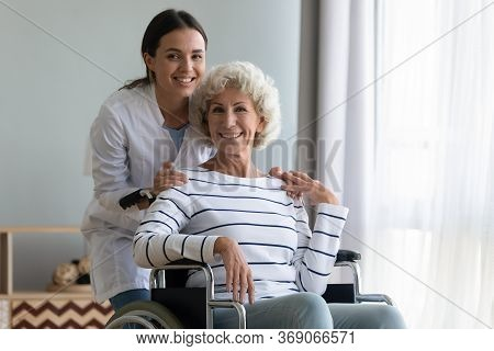 Portrait Of Satisfied Elderly Patient In Wheelchair And Caring Caregiver