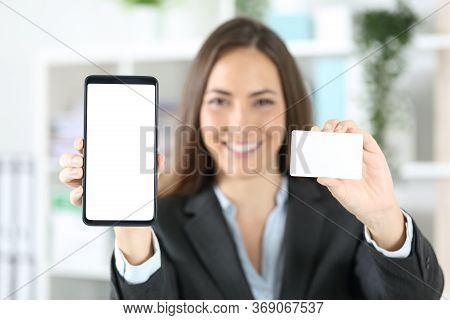 Front View Of An Unfocused Happy Executive Woman Shows Blank Credit Card And Smart Phone At The Offi