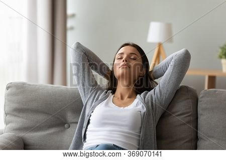 Calm Woman Puts Hands Behind Head Relaxing Seated On Couch