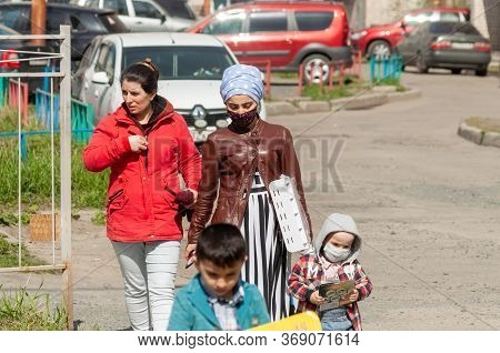 Petrozavodsk, Russia - 24 May 2020. Migrant Woman Wearing A Protective Mask With Children On A City