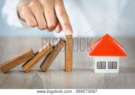 Woman Hand Stopping Risk The Wooden Blocks From Falling On House, Investment Risk And Uncertainty In