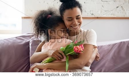 African Mom Hugs Daughter Express Gratitude For Attention And Flowers
