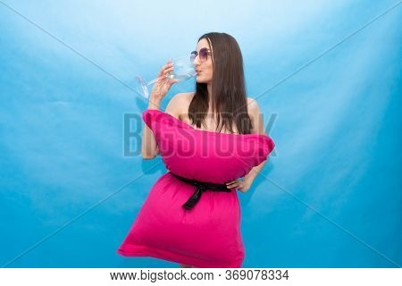 Happy Woman In Pink Pillow Dress And Sunglasses Drinks A Glass Of Champagne On A Blue Background For