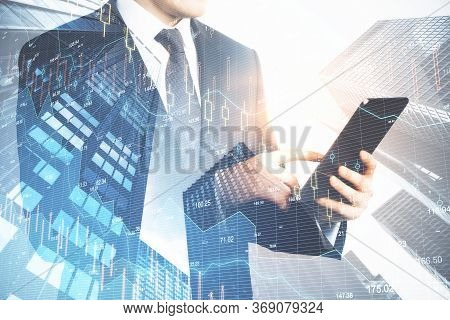 Businessman Holding Tablet And Digital Falling Chart Hologram On City Background. Business Crisis Co