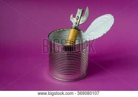 Old Can Opener In An Empty Tin Can On A Purple Background. Open Tin Can With White Food Enamel Insid