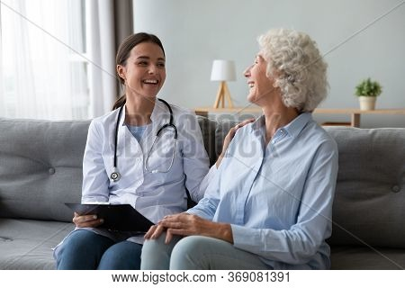 Friendly Nurse Laughing With Elderly Female Patient During Homecare Visit
