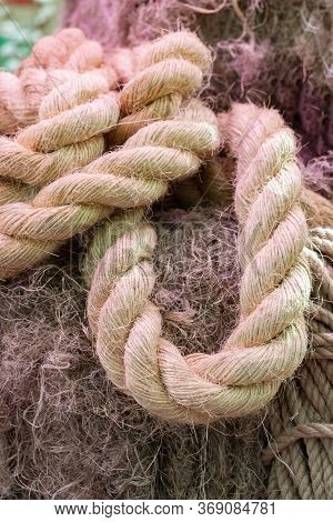 A Thick Twisted Rope Made Of Natural Hemp, A Loop Of Thick Rope Made Of Plant Material. Nautical Rop