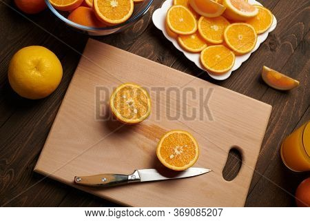 Fresh orange fruit whole and sliced on a wooden table, cutting board and kitchen knife. A plate full of citrus slices - natural and healthy food. Glass of fruit cocktail.