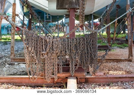 A Rusty Anchor Chain Hangs From A Rope In Winter Storage.