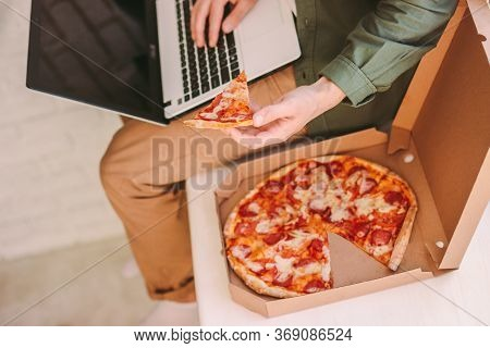 Top View Stylish Hipster Man Typing Laptop Keyboard, Hold Slice Of Tasty Pizza, Surf Internet At Coz