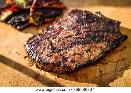 Grilled Juicy Marinated Angus Beef Flank Steak On Wooden Board.