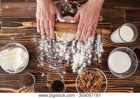 Woman Is Rolling Pin On Dough In Kitchen, Dough Recipe Ingredients And Rolling Pin On Vintage Wood T