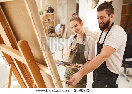 Warm Toned Portrait Of Creative Couple Painting Picture Together And Smiling Happily While Standing
