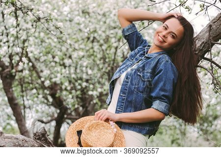 Portrait Young Carefree Hippie Girl Posing With Her Long Brunette Hair And Smiling On Spring Meadow
