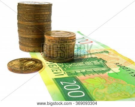 Piles Of Russian Coins Of Ten Rubles Stand On A Bill Of Two Hundred Rubles. Not Isolated. News Of Mi