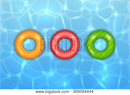 Float Rings On Blue Water Pool Background. Summer Aqua Background With Three Colored Swim Rings. Let