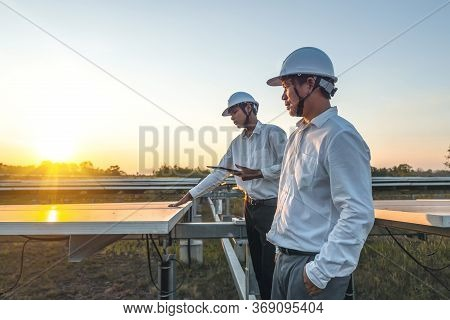 The Solar Farm(solar Panel) With Two Engineers Walk To Check The Operation Of The System, Alternativ