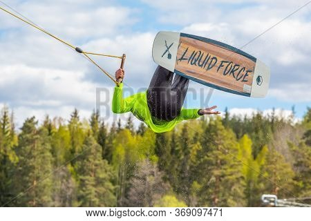 Fagersta, Sweden - Maj 26, 2020: Wakeboarder Teen Boy Make An Extreme Jump On Wakeboard, Around Ther