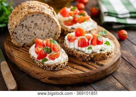 Italian Antipasti Bruschetta With Tomato, Basil And Ricotta Cheese On Wooden Serving Board. Closeup