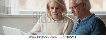 Aged Couple Read Bank Statement Analyzing Family Expenses Feels Concerned