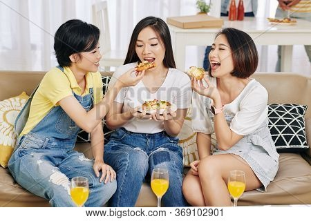 Cheerful Pretty Female Friends Sitting On Sofa And Eating Delicious Pizza At House Party