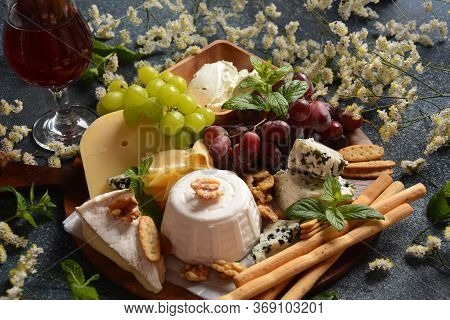Cheese Platter With Assorted Cheeses, Grapes, Nuts And Snacks . Italian, French Cheese Starter. Trad