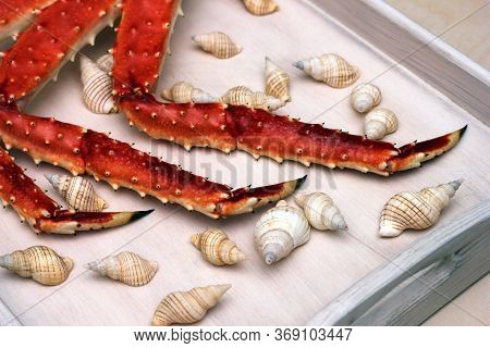 Legs Of A Boiled Crab On A Wooden Tray Among The Shells. Delicious Seafood.